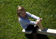 Smiling girl on a wooden see-saw.