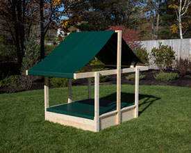Cedar sandbox with sand and shade cover.