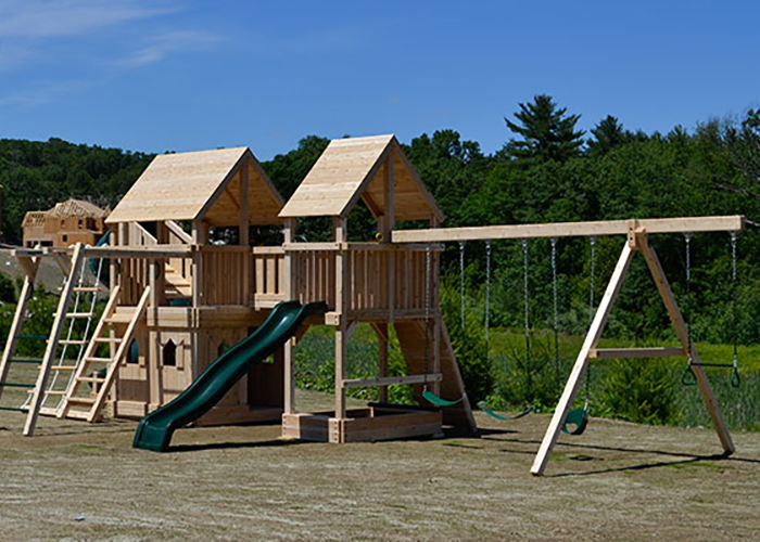 Two cedar play sets connected with a wooden bridge in the backyard of a Holliston, MA home.