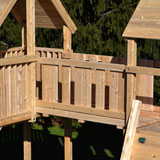A bridge connecting two cedar swing set forts.