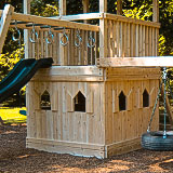 A cedar clubhouse with floors under a swing set fort.