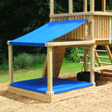 Large sandbox with sand and shade covers attacted to a cedar swing set fort.