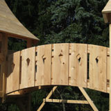 A arched bridge connecting two cedar swing set forts.
