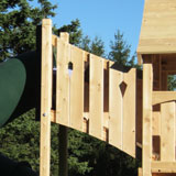 A tower with diamond cut-outs attacted to a cedar swing set fort.