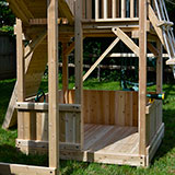 Lower cedar half walls with lower floors under a swing set fort.