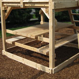 A cedar Picnic table under a playset fort.