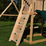 Narrow wooden swing set rock wall with green rock holds.