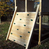 Wide wooden swing set rock wall with green rock holds.