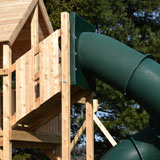A tower attacted to a cedar swing set fort.