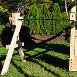 A wooden swing set arm with a steel pipe for turning.