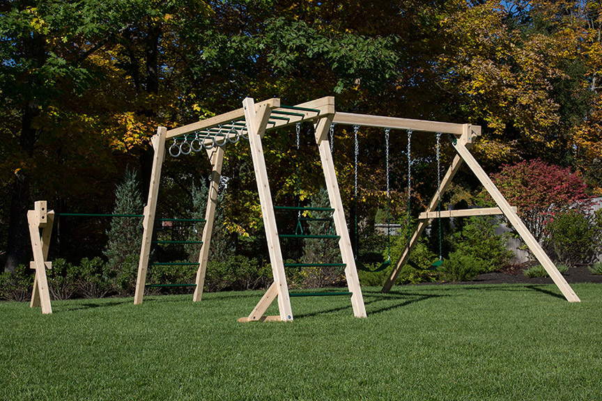 Cedar swing sets with rock wall and rope ladder.