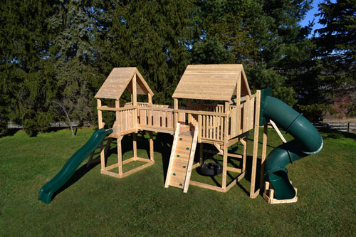 Cedar swing sets with two forts connected with a bridge, includes swings and slides.