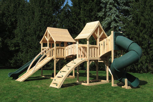 Cedar swing set with two forts connected with a arched bridge with a green tube slide.